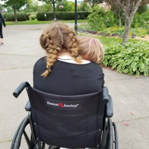 Two girls sharing a wheelchair