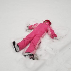Child making snow angels in snow