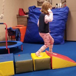 Girl playing on foam blocks